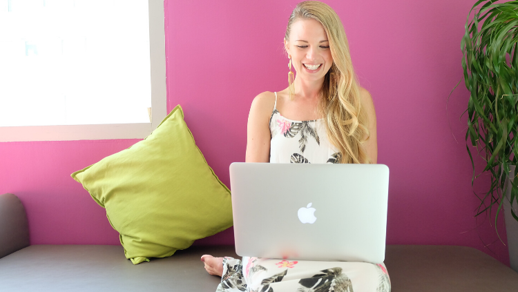 woman smiling while looking at a laptop
